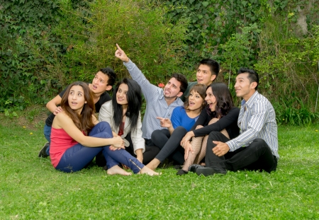 Happy group of students sitting at the park  photo