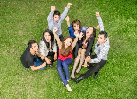 cheering group of friends holding hands up outdoors photo
