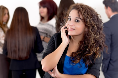 Hispanic woman using a cellphone with peers photo