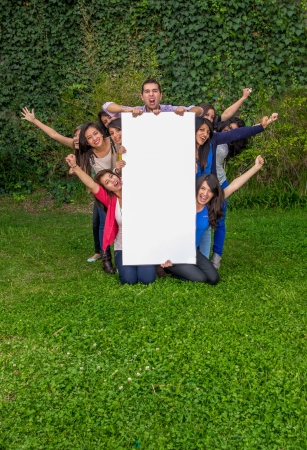 Group of friends holding blank sign outside photo
