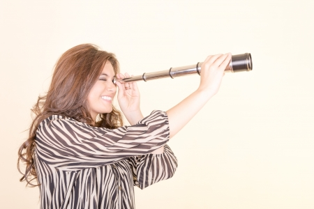 Young woman using telescope