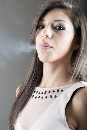 Elegant brunette woman smoking a cigarette on black background photo