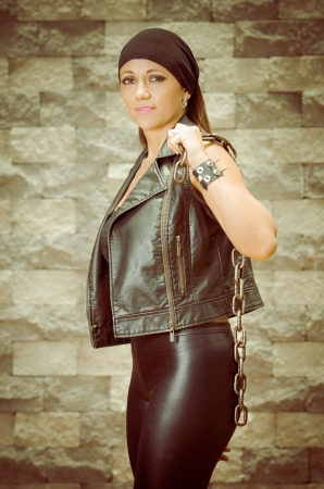 A young and beautiful latina gang woman in leather photo