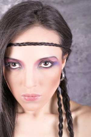 Hippie girl with purple makeup and breaded hair on forehead photo