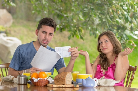 couple having breakfast fighting  at home with garden in the background photo