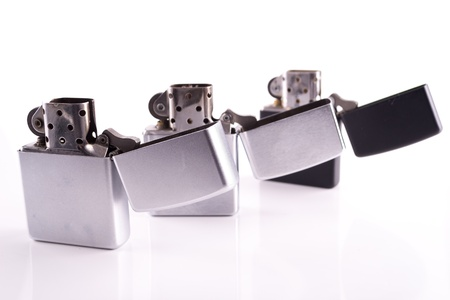 Silver metal lighters on white photo