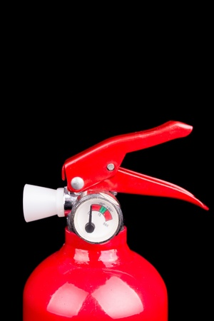 A red fire extinguisher isolated on a black background photo
