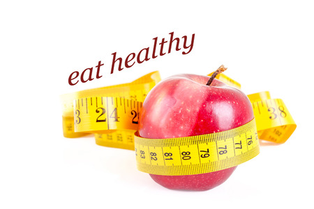 Dieting concept   apple with measuring tape on white background photo