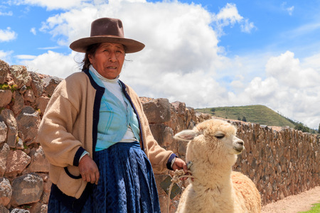 inhabits: RAQCHI PERU -JANUARY 15: Unidentified Quechua indian woman with lama inhabits at Raqchi Ruins, Peru on January 15, 2013. Raqchi Ruins is a popular destination for tourism from all around the world. Editorial