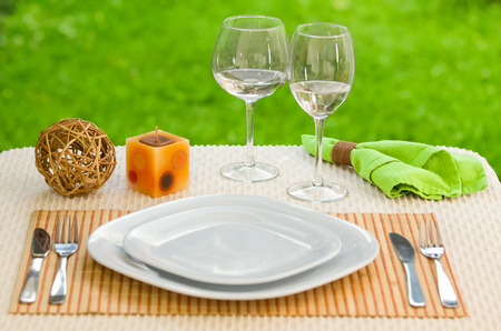 Empty plate with fork and knife against meadow. Table arrangement. photo