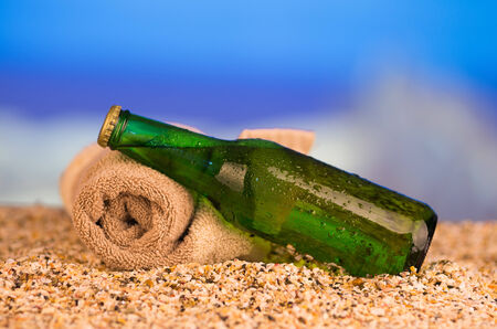 Ice cold green unlabelled bottle of refreshing lager or soda standing upright in the golden sand on a tropical beach under the hot rays of the summer sun photo
