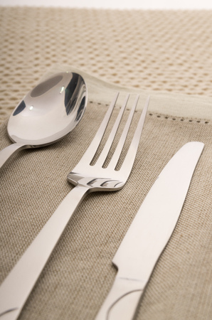 Knife, fork and spoon with linen serviette photo
