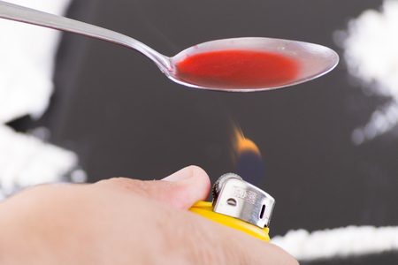 risky behavior:  heating drugs in a spoon over a flame Stock Photo