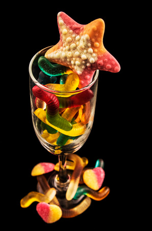 gummie: gummy bears  and a wine glass on a dark background