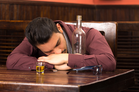 man in suit drunk and sleeping on a table photo