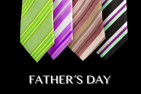 four colored ties with fathers day text isolated over black photo