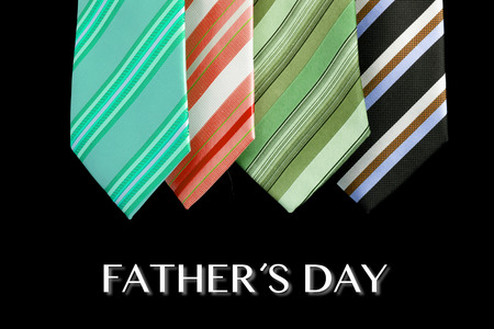 colored ties with father s day text isolated on black photo