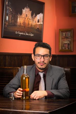 drinking alcohol: hispanic man in suit drinking alcohol shot  Stock Photo