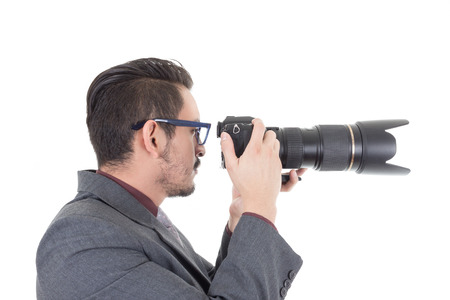 young man in suit taking a photo with professional camera isolated over white photo