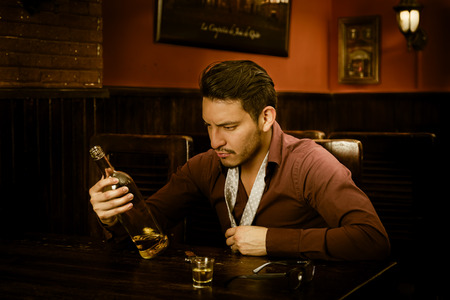 undone: latin guy drinking shots and staring at bottle