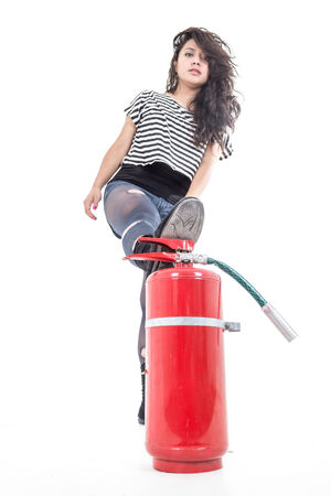 young girl with leg on fire extinguisher  isolated on white photo