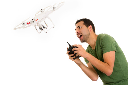 young latin man with playing quadcopter drone isolated on white