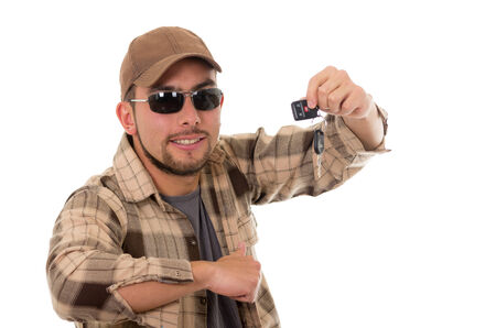 outdoorsman: happy young guy in flannel shirt and cap showing car keys in his hand isolated on white