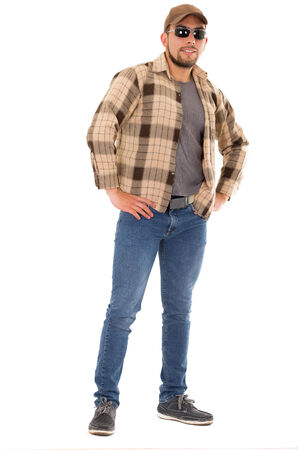 confident latin man in flannel shirt cap and sunglasses standing fullbody isolated on white photo