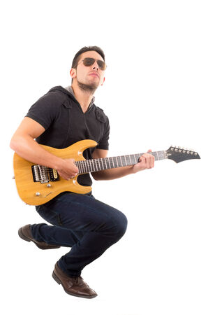 latin young musician crouching playing electric guitar isolated over white photo