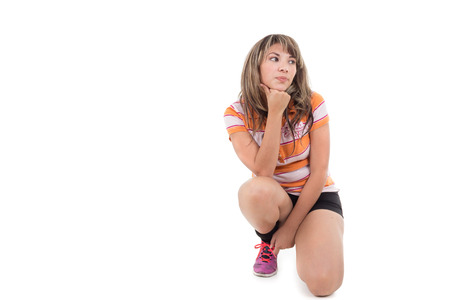 hispanic girl kneeling with hand on her chin isolated on white Stock Photo