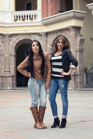 two casual hispanic girls posing with hand on hip outdoors photo