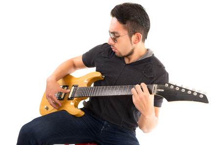 hispanic young man sitting playing electric guitar isolated over white photo