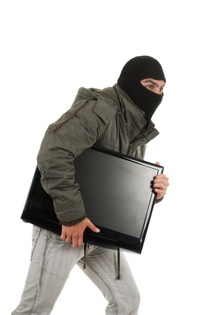 young thief wearing black hood and jacket carrying a monitor isolated on white photo