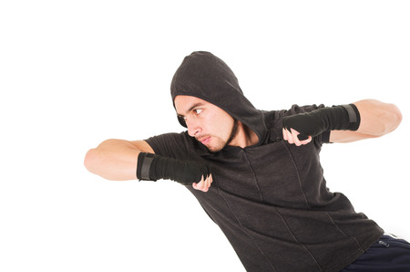 elbow band: young fighter man wearing black hoodie hitting with elbow isolated over white Stock Photo