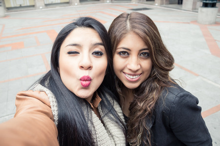 hot kiss: two latin girls taking a selfie outdoors Stock Photo