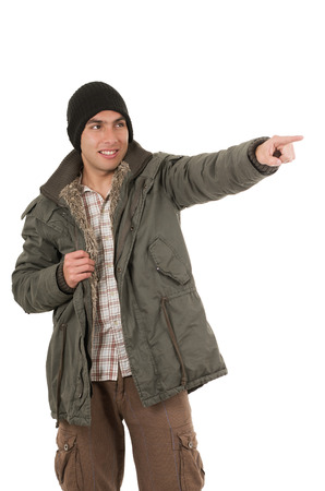 young man wearing green winter coat and a beanie pointing with finger isolated on white photo