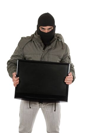 young thief wearing black hood and jacket carrying a television isolated on white photo