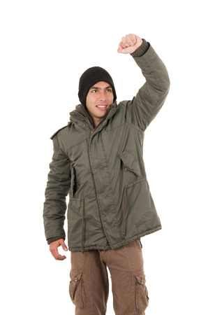 winner young man wearing green winter coat and a beanie with one fist up isolated on white photo