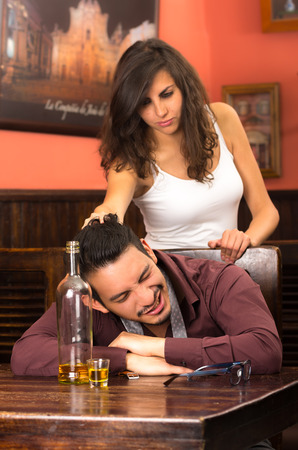 drunk young man sleeping and angry girlfirend in a bar pulling his hair