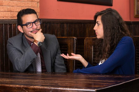 nagging: young latin couple woman nagging her boyfriend in a restaurant Stock Photo