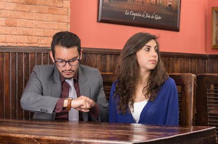 若いカップルはレストランでウェイターを待っています。