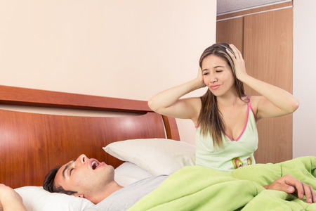 young man snoring in bed and wife cant sleep  photo
