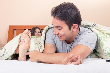 tickling: cute young man tickling girlfriends  feet in bed  Stock Photo