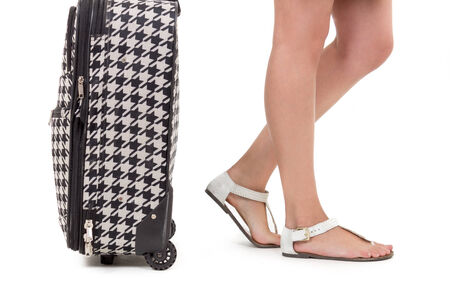wearing sandals: closeup of suitcase and girl s feet wearing sandals isolated on white