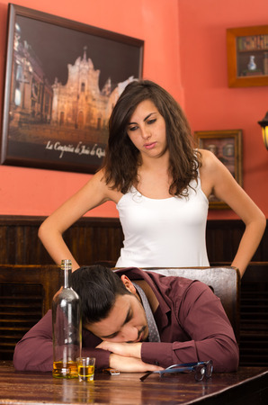 drunk young man sleeping and angry girlfirend in a bar photo