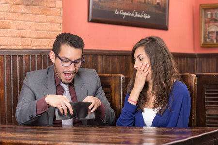 young couple with no money to pay the bill in a restaurant photo