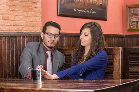girlfriend prohibits boyfriend to drink alcohol from hip flask in a restaurant Stock Photo