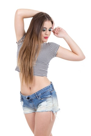 shorts t shirt sexy: beautiful blond girl with long hair posing looking down wearing shorts and crop top isolated