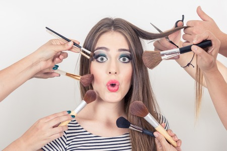 artist's model: closeup of surprised beautiful blond girl getting makeup done by many people isolated