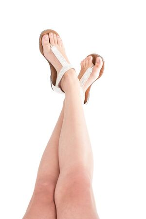 wearing sandals: woman s legs wearing sandals isolated on white